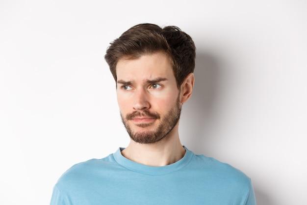 Primo piano di un uomo triste deluso, che fa una smorfia e si acciglia, sembra sconvolto, in piedi dubbioso su sfondo bianco.