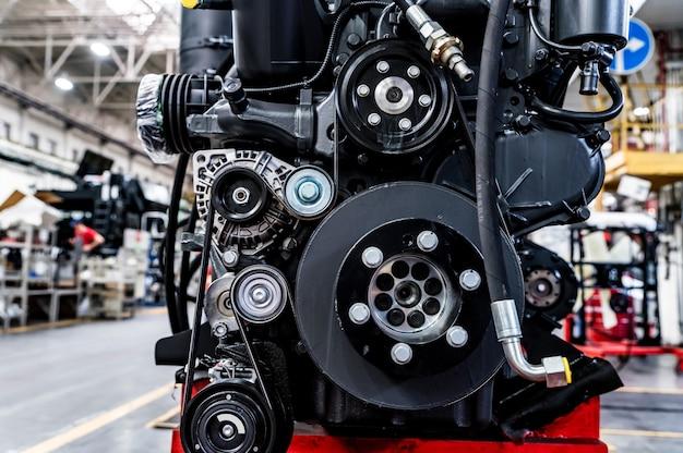 농업 공학 산업에서 현대 트랙터에 분해 된 트랙터 부품을 닫습니다. 연소 엔진. 트랙터 및 콤바인 어셈블리 섹션. 선택적 초점.