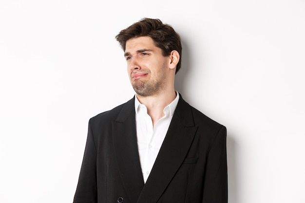 Primo piano di un giovane disgustato in abito alla moda, che fa una smorfia sconvolto, guarda a sinistra e in piedi su sfondo bianco.