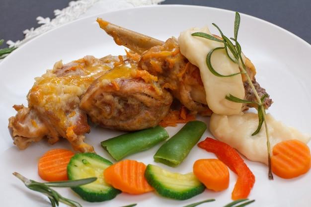 야채와 로즈마리와 함께 세라믹 접시에 베샤멜 소스와 함께 화이트 와인에 구운 토끼 다리의 클로즈업 요리. 오븐에서 요리한 식이 토끼 고기.