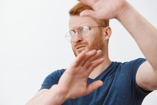 Primo piano dell'uomo adulto dispiaciuto con gli occhiali che copre il viso con le mani dalla luce, difendendosi