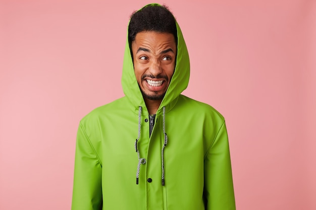 Close up of displeased angry young handsome african american handsome guy in green rain coat , stands, bursts his teeth aggressively