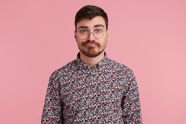 Close up of displeased young bearded man in glasses, wearing in colorful shirt, isolated over pink background and looking at camera with a raised eyebrow. people and emotions concept.