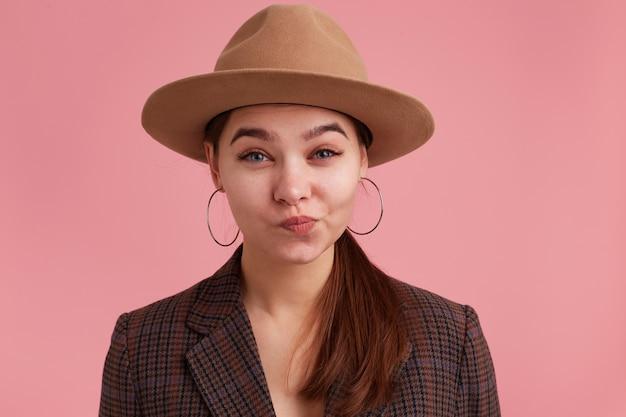 Close up scontento giovane donna arguzia arco labbra, sopracciglia indignate sollevate. guardando la fotocamera isolata su sfondo rosa.