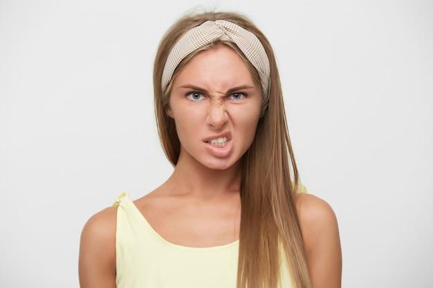 Close-up di scontento giovane bella signora bionda con acconciatura casual torcendo la bocca e le sopracciglia accigliate mentre posa su sfondo bianco, indossa fascia beige e top giallo