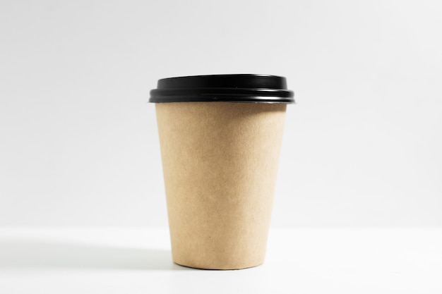 Close-up of disposable paper cup for coffee take away, with black lid, isolated on white.