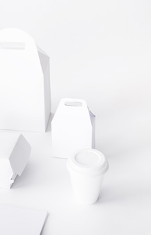 Close-up of disposal cup and food parcel mock up on white background