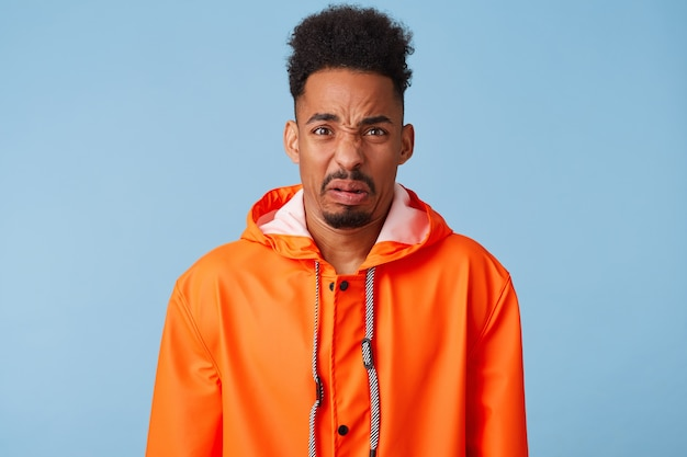 Close up of dissatisfied young african american dark skinned male wears in orange rain coat, frowns and looks with disgust, feels upset, stands.