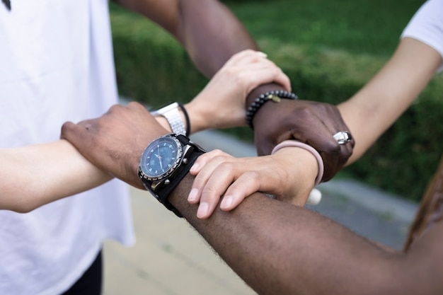 Close up diverse friends holding arms