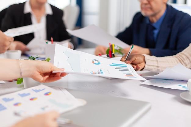 Primo piano di diversi colleghi della società di avvio che si incontrano in un luogo di lavoro professionale