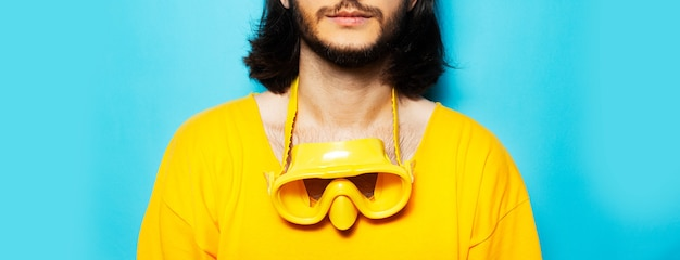 Close-up of diving mask on neck of young man in yellow on blue background.