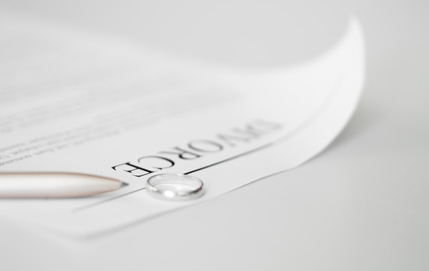 Close-up divorce contract with rings on table