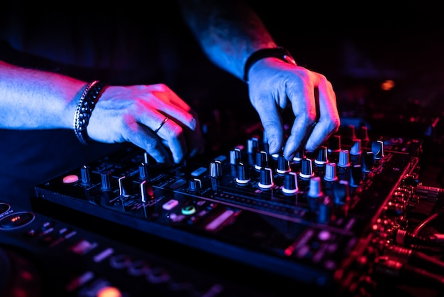 Close up of dj hands controlling a music table in a night club.