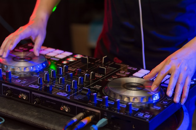 Close up of dj hands on stage mixing, disc jockey and mix tracks on sound mixer controller, playing music at bar, disco tech or night club party.