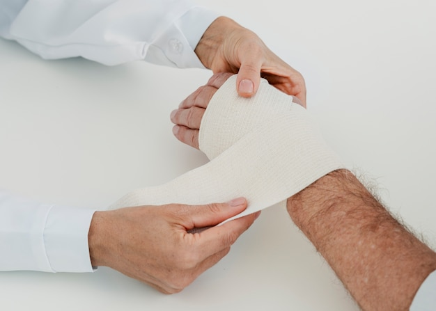 Close-up doctor bandaging hand of patient