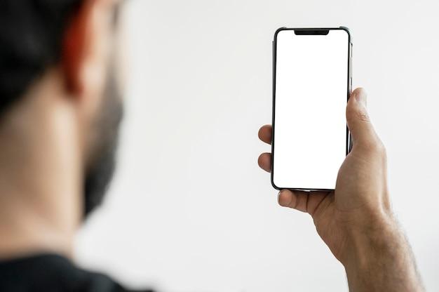 Крупным планом доктор просматривает мобильный телефон