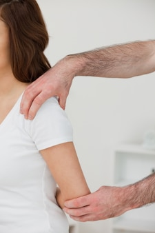 Close-up of a doctor examining the shoulder of a patient