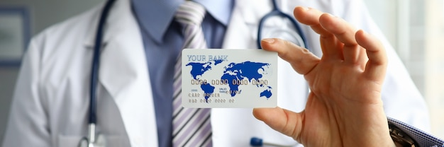 Close-up of doctor hand holding plastic credit bank card. practitioner in uniform with stethoscope. method of payment for services in private clinic. medicine and health insurance concept