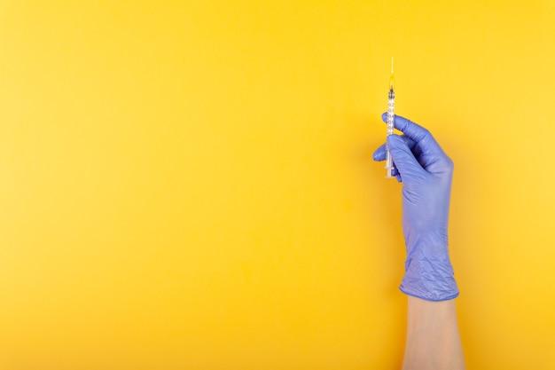 노란색 배경에 주사기를 들고 의료 장갑에 의사 손을 닫습니다