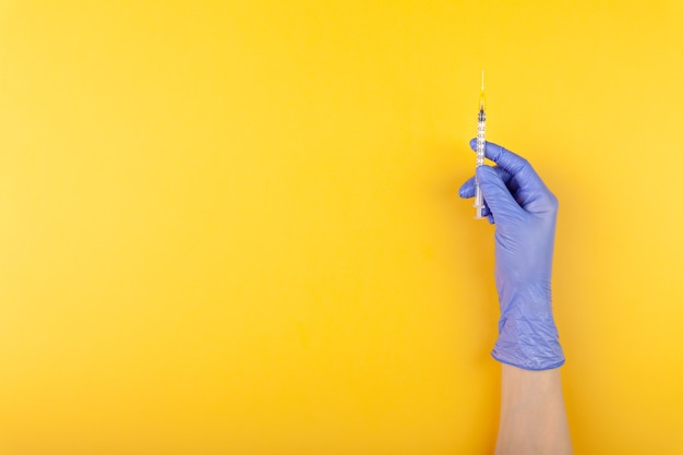 Close up doctor hand in medical glove holding syringe on yellow background