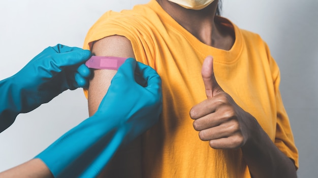Close up doctor hands with glove putting plaster on female patient's shoulder after vaccination.