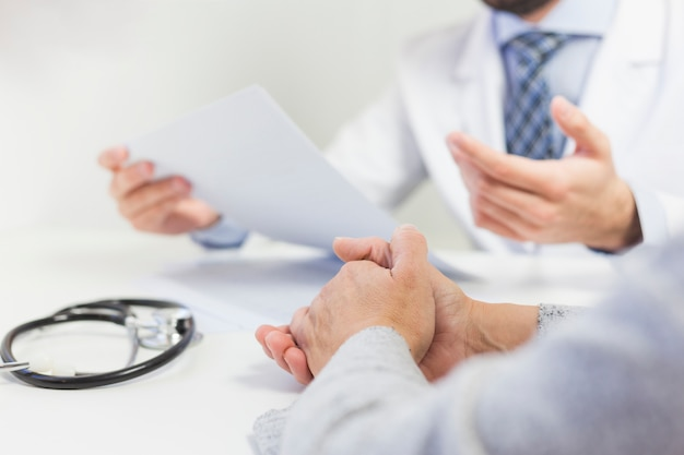 Close-up of a doctor in his office discussing medical report with patient
