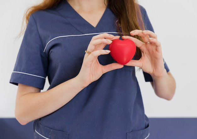 Close-up doctor holding heart shaped toy