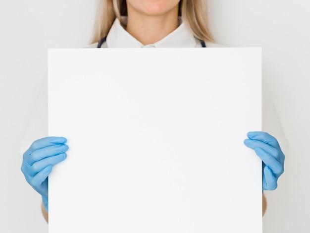 Доктор крупным планом держит бумагу