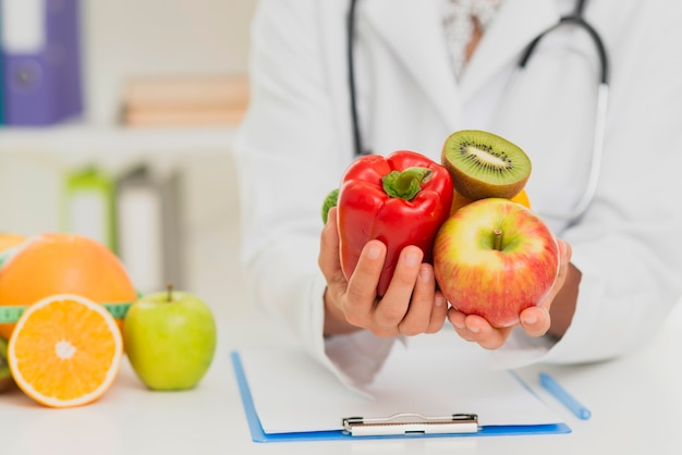 Close-up doctor holding up fruits and vegetables
