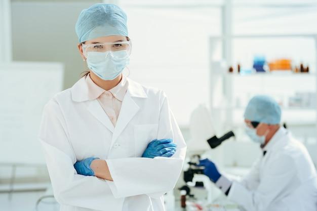 Закройте вверх. врач в защитной маске, стоя в лаборатории. фото с копировальным пространством.