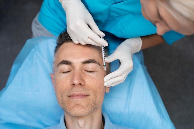 患者を注射する医師をクローズアップ