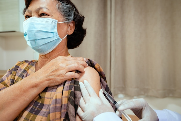 Close up on doctor is injecting vaccination on senior woman arm. adult patient wearing protective face mask for protect coronavirus covid-19 pandemic. health care and medical concept.