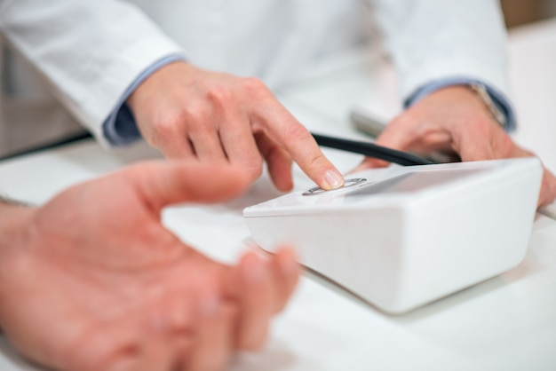 Close-up of doctor measuring patient's blood pressure.