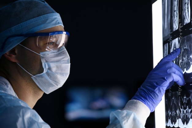 Close-up of doctor in medical uniform examines x-ray on computer screen. professional worker check-up skiagram of human body. modern technology and medicine concept