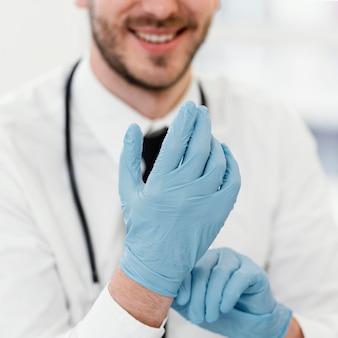 Medico del primo piano che indossa i guanti
