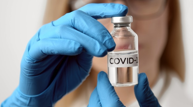 Close-up of doctor's hands in gloves holding vaccine bottle with covid-19 inscription, focus on vial