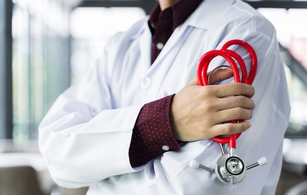 Close up doctor stood and crossed arms with a stethoscope at the hospital.