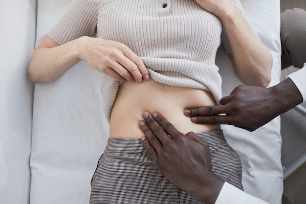 Close-up of doctor touching the stomach of the woman and holding medical exam