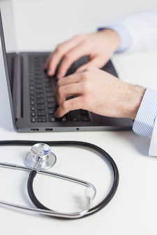 Close-up of doctor typing on laptop with stethoscope on white desk