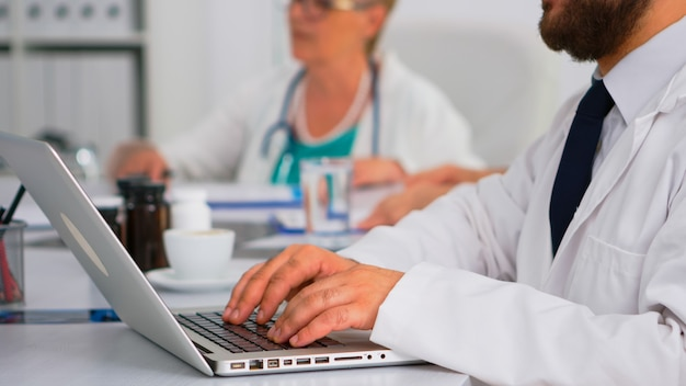 Close up of doctor using laptop, writing treatment informations while coworkers discussing in background during medical conference sitting at desk in hospital office. team of doctors brainstorming