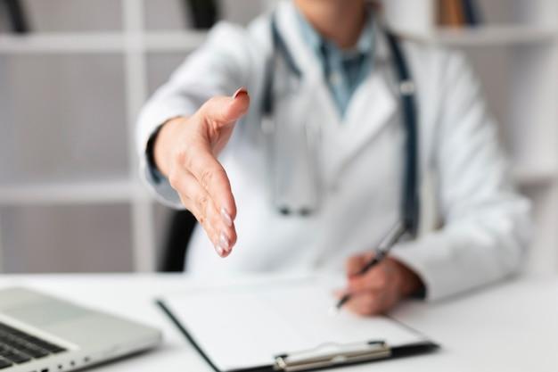 患者の手を振るのを待っているクローズアップ医師
