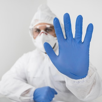 Close-up doctor wearing a face mask and surgical gloves