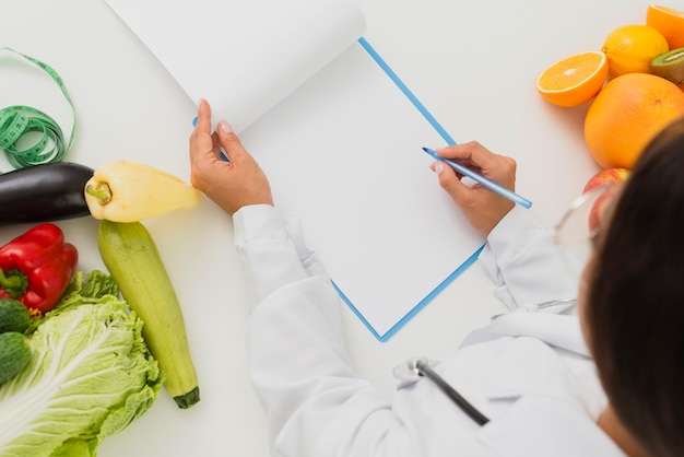 Close-up doctor with fruits and vegetables writing