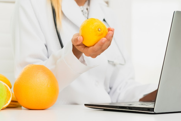 Close-up doctor with lemon and laptop