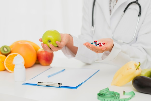 Close-up doctor with pills and fresh fruits