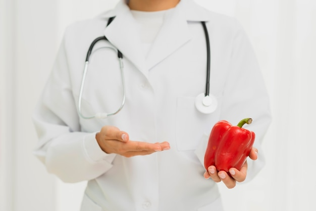 Close-up doctor with stethoscope and bell pepper
