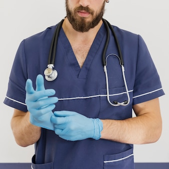 Close-up doctor with stethoscope and gloves
