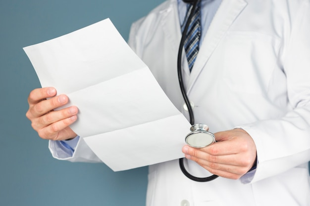 Close-up of doctor with stethoscope holding medical report in hand
