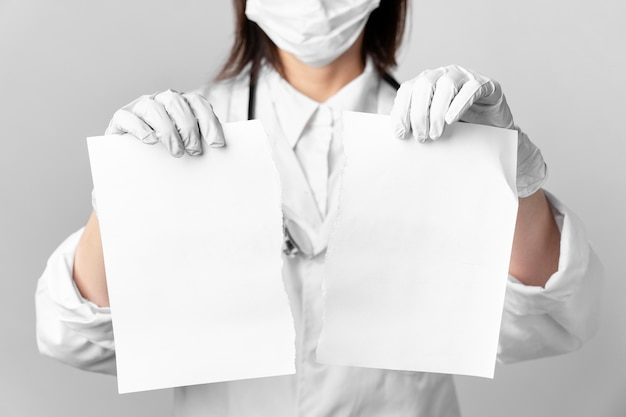 Close-up doctor with surgical mask holding papers