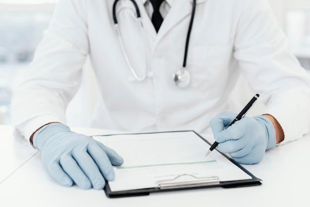 Primo piano medico che scrive su carta